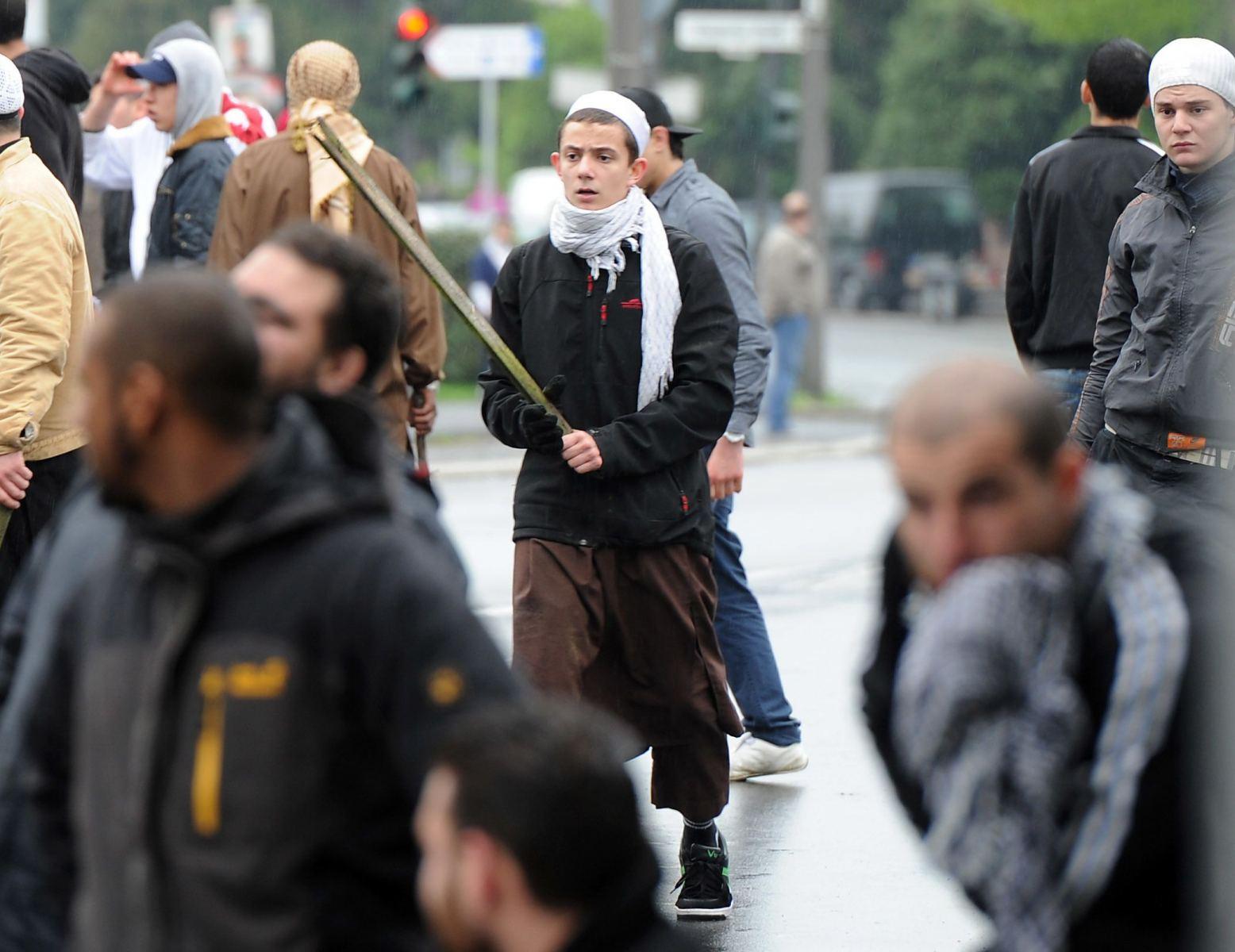 Ein mit einer Latte bewaffneter islamistischer Demonstrant steht am Samstag (05.05.2012) bei einer Protestkundgebung gegen eine Wahlkampfveranstaltung der rechtsextremen Splitterpartei Pro NRW vor der König Fahd Akademie in Bonn in der Menge. Etwa 25 Pro NRW-Anhängern standen 300-400 Gegendemonstranten gegenüber. Foto: Henning Kaiser dpa/lnw  +++(c) dpa - Bildfunk+++ |
